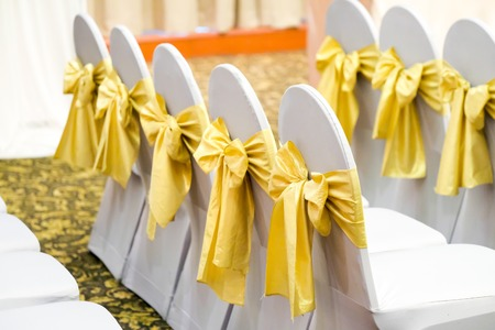 Row of white chairs decorated with gold ribbons