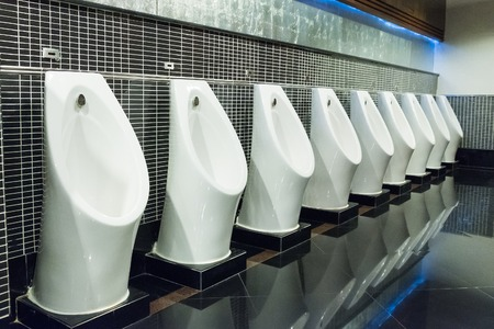 ceremic: white urinal in men public toilet with black wall tile Stock Photo