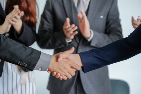 Group of business people meeting shaking hands together, business outdoor meeting concept.
