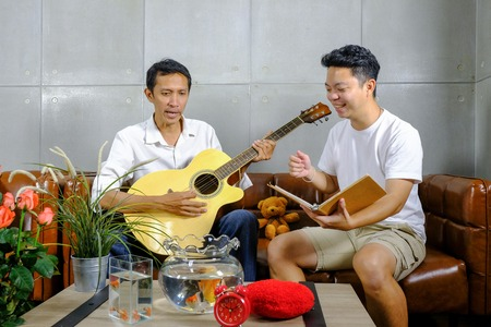 Two friends man playing musical instruments cheerfully