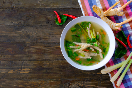Spicy chicken legs Soup in white cup on wooden table Stock Photo