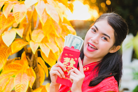 The girl in the red dress of Chinese descent is happy with the red envelope with the dollar.