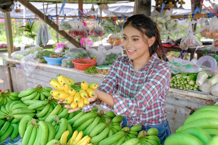 Woman trader sells vegetables, fruits and bananas that are ripe yellow in a rural roadside shop in Thailand. Stock Photo