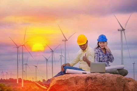 Happy Asian Female and male engineers writing the note pad on Wind turbine power generator with world map at twilight time, industrial concept