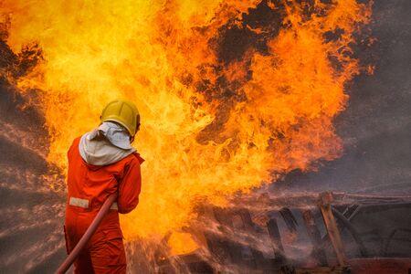 El bombero está utilizando agua en la operación de extinción de incendios Foto de archivo