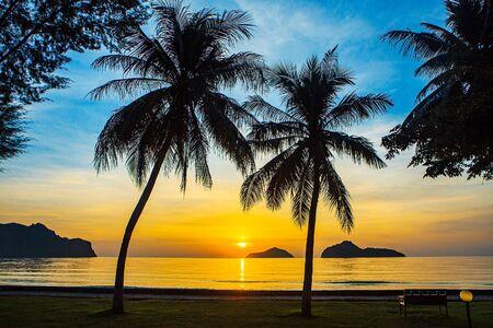 Salida del sol en el mar con islas y cocoteros. Foto de archivo