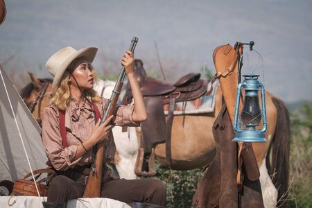 A beautiful Asian cowboy who takes care of her gun and horse with love while at the camp. Zdjęcie Seryjne