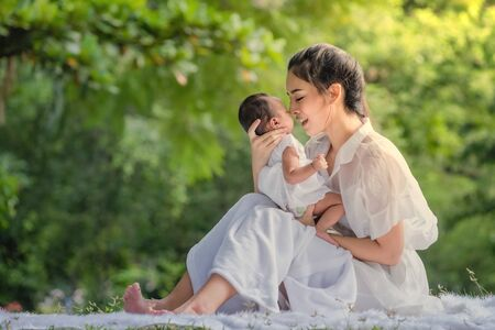 Beautiful mother and baby in an Asian park Stock Photo