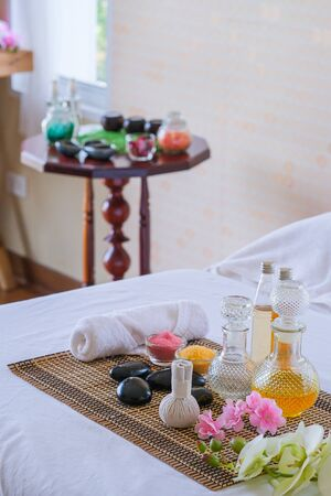Spa treatment set and aromatic massage oil on bed massage. Thai setting for aroma therapy and massage with flower on the bed, relax and healthy care. Reklamní fotografie