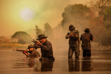 The rangers wade through the water to randomly shoot and attack. Stock Photo