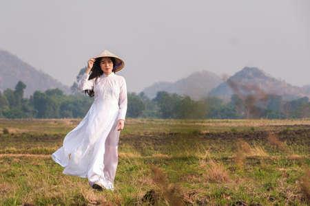 Vietnamese girl in white dress wearing a hat walks in the field