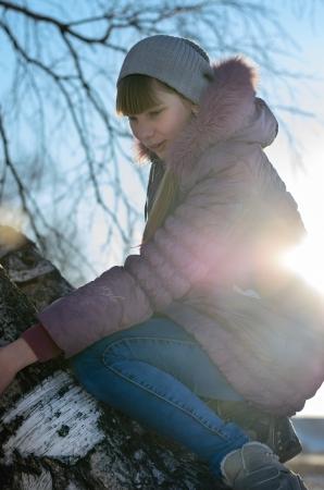 romp: The girl climbed on tree sunny autumn evening.