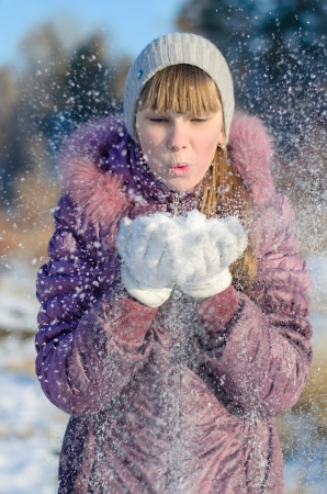 he is different: Girl blowing on snow in her hands and he scatters in different directions. Stock Photo