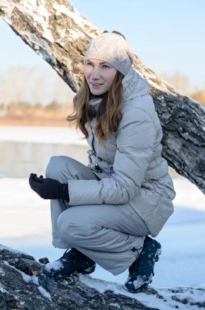 climbed: Beautiful girl on winter shore climbed a tree.