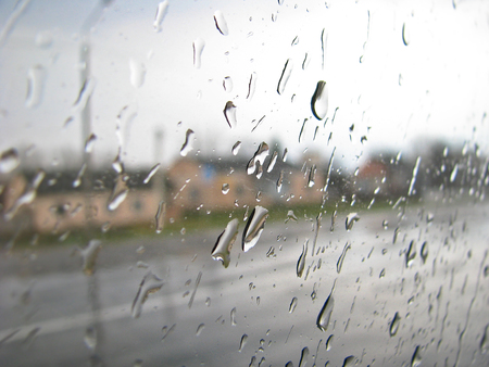 Drops on the glass of the car trip. Heavy rain outside the window on the background of the city, village. Stock Photo