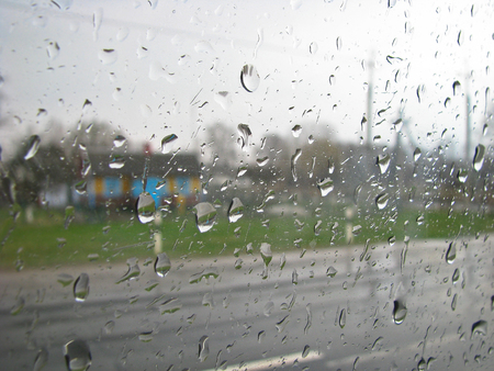 car glass Drops road. Heavy rain outside the window on the background of the city, village.