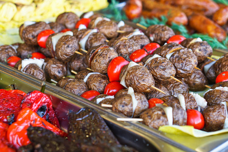Dinner table with meat grill, roast new potatoes, vegetables, salads, sauces, snacks and lemonadeб Grilled sausage, mushrooms. Stock Photo