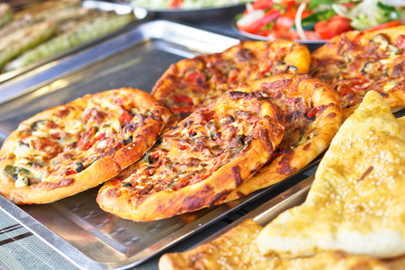 Ready pizza with meat and sausage background with vegetables. Summer holidays and food in nature. Stock Photo