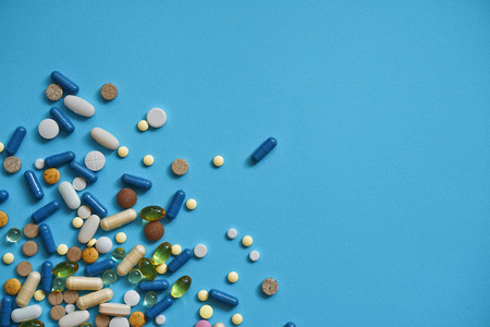 Spilled colored medications and pills on a blue background. Pharmacology and medicine struggle for health. Drug addiction. Treatment of various diseases Stock Photo
