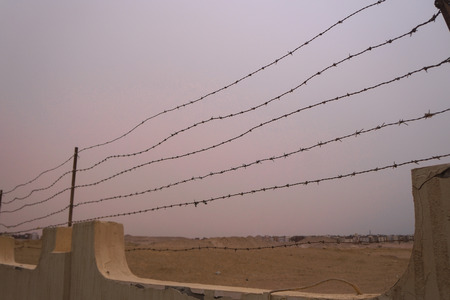 Restrictive fence with barbed wire. Tour area conc camp. Genocide during the war. Stock photo Stok Fotoğraf