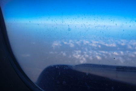 Airplane window in the air. Blurred clouds below. Illuminator transport aircraft. Tourist background