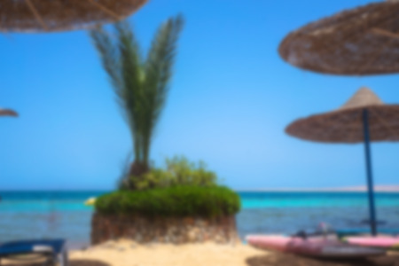 Blurred landscape on the sunny sea or ocean. Beautiful beach with sun loungers and umbrellas. Tourist background Stok Fotoğraf