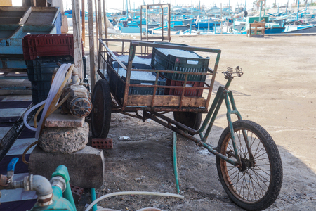 An old broken bike loaded with ice crates in the tropics. Egyptian market in all its glory. Slum poverty