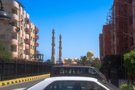 Egyptian city streets. Muslim mosque on the background of houses and roads, countries of Asia and Egypt. Stock photo for design
