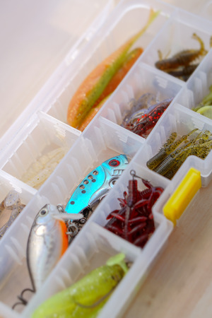 Colorful silicone fishing baits with plummets on wooden table. Various fish and worms and crayfish. Toned image and top view. Stock background, photo
