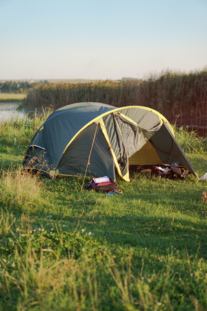 Landscape with a tent with a beautiful view near the river. Spring summer outdoor recreation. Stock background, photo