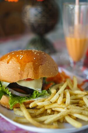 Burger and french fries on the table. Delicious food fast food. American food in a cafe