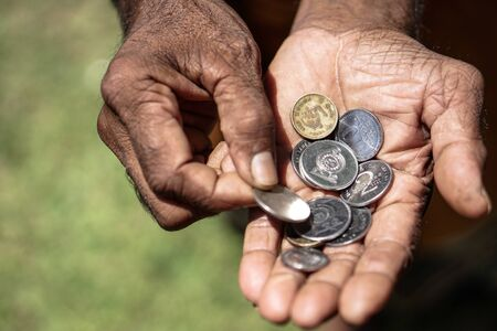 Coins in dark working hands. Beyond the poverty line in Asian countries. Subject soap bar.