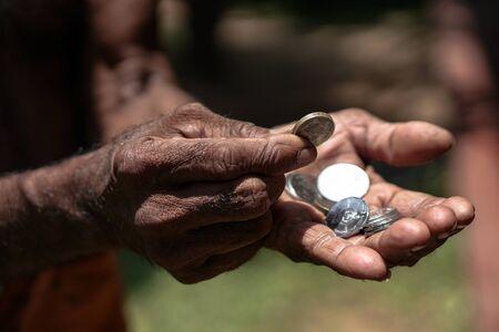 Münzen in dunklen Arbeitshänden. Jenseits der Armutsgrenze in asiatischen Ländern. Thema Seifenstück.