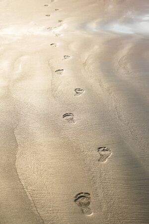 Footprints of bare feet on the sand of the beach. The coast of the ocean, the sea. Tourist background for travel agency. Stock photo