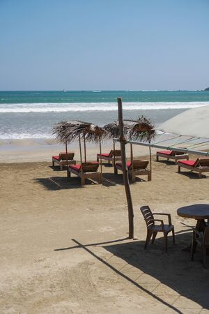 Beautiful Sri Lankan view of the Indian Ocean with sun loungers on the beach. Summer holidays in Asia. Stock photos
