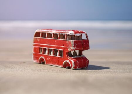 Red toy bus in nature pollutes the earths ecosystem. English bus without wheels. Consumer world without environmental concerns