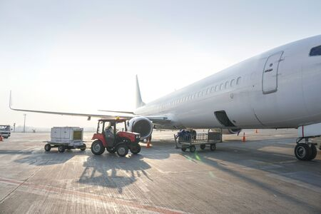 Passenger aircraft at the airport near the terminal. Unloading and loading baggage. Stock photo Фото со стока
