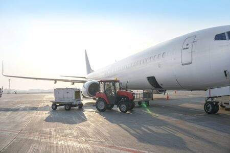 Passenger aircraft at the airport near the terminal. Unloading and loading baggage. Stock photo Stock Photo