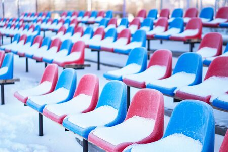 Snow-covered multi-colored seats in the stadium in winter. Snowfall interferes with sports. Uncleaned stadium. ecological disaster freeze Stok Fotoğraf