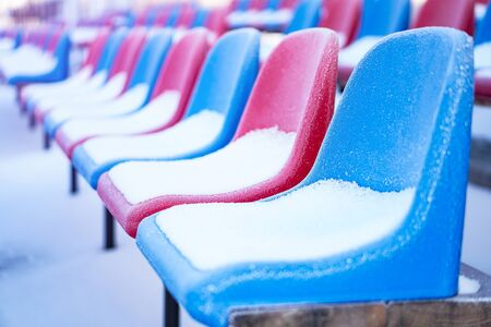 Snow-covered multi-colored seats in the stadium in winter. Snowfall interferes with sports. Uncleaned stadium. ecological disaster freeze Stockfoto