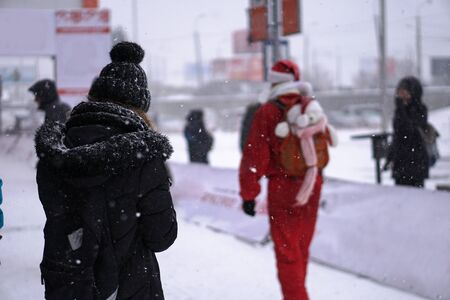 Gray people crowd in winter and only one person in a Christmas hat. Stow background Stock Photo