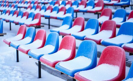 Snow-covered multi-colored seats in the stadium in winter. Snowfall interferes with sports. Uncleaned stadium. ecological disaster freeze Фото со стока