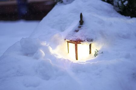 Beautiful winter composition in the snow. The lantern shines in the snow on the eve of Christmas and New Year. Background for design.