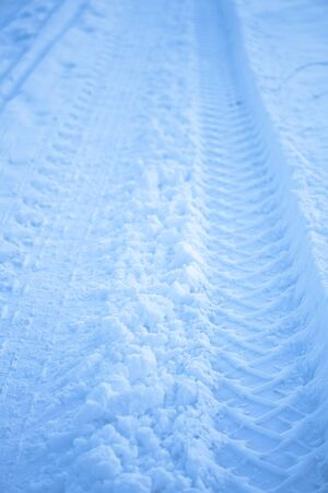 Tread texture of car wheels on snow. Winter road in January, December. Rural area and background of tractor tracks in the snow 免版税图像