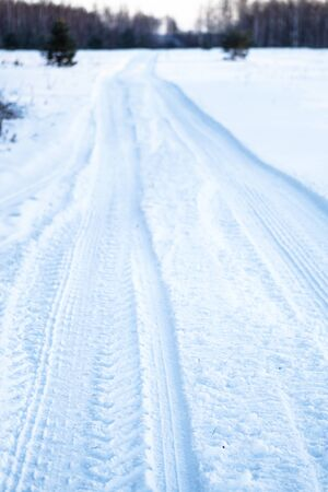 Tread texture of car wheels on snow. Winter road in January, December. Rural area and background of tractor tracks in the snow Stok Fotoğraf
