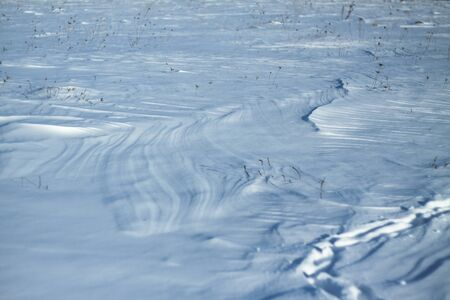 Snow-white snow and the earth sheltered by it. Countryside and snowfall. Winter dunes and mountains of snowflakes. Stock background.
