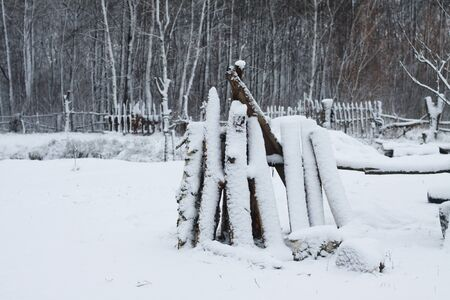 Winter landscape with harvesting firewood in the forest. Forest sawmill and logs covered with snow. Stock photo for design Zdjęcie Seryjne