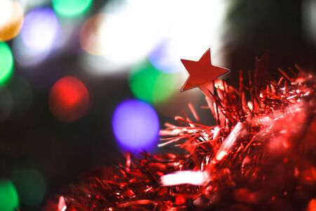 Beautiful Christmas red star on a background of bokeh garlands. Christmas theme design