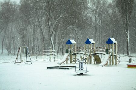 Playground covered with snow. Winter collapse in the city. Ecological catastrophy