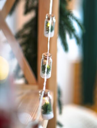 Beautiful Christmas garland in decorative jars on a bokeh background. Christmas theme design Imagens